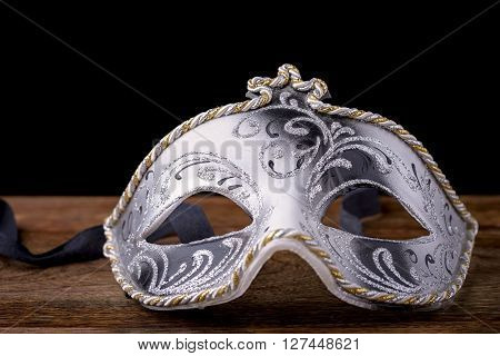 Venetian mask carnival white, black and gold on wood on a black background poster