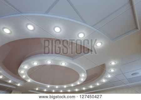 Modern layered ceiling with embedded lights and stretched ceiling inlay light turned on