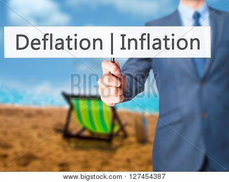 Deflation Inflation - Businessman Hand Holding Sign