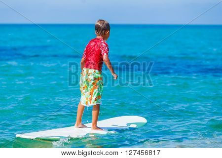 Young surfer boy is riding a wave.
