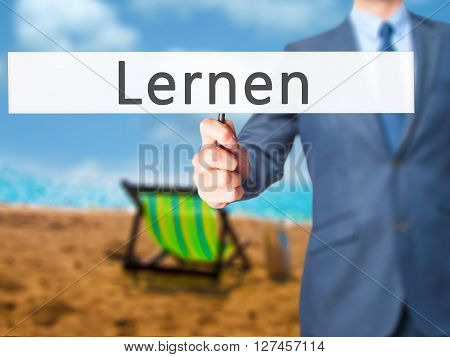 Lernen (learn In German)  - Businessman Hand Holding Sign
