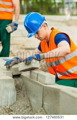 Image of manual worker with setts paving road