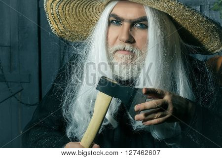 Bearded senior man in long white wig and straw round hat with axe on wooden background