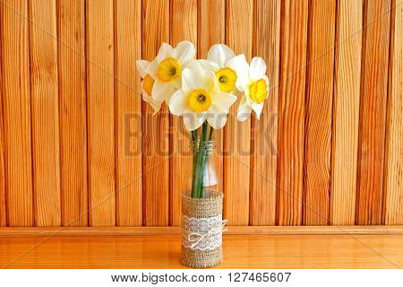 Five yellow daffodils in a vase. Wooden background