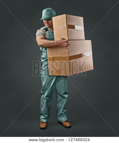 delivery man in green uniform holding a box on a gray background