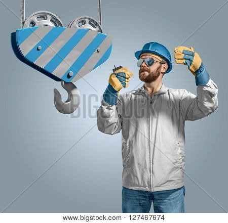 worker builder in helmet manages the construction process, crane hook on the isolated background poster
