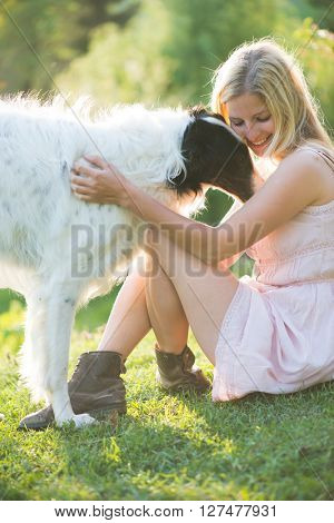 Happy blonde woman playing with her Russian wolfhound dog in garden