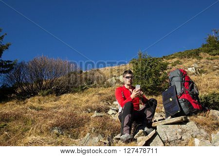 The guy in the mountains, hike with a backpack, and a solar panel for charging accumulators.