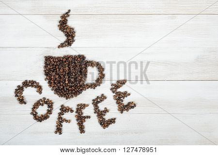 Coffee beans making a word coffee and shape of cup of fragrant hot coffee on wooden background