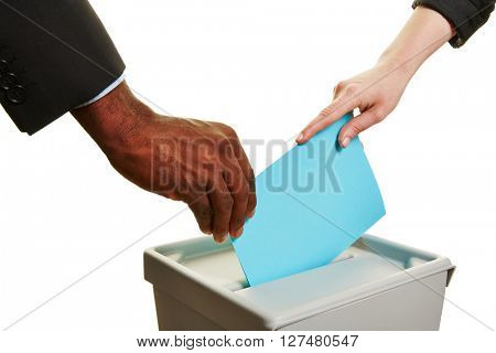 Hands holding ballot paper during election over a ballot box