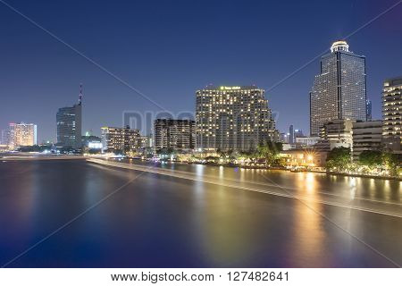 River View With The Lights, Boats And Modern Buildings At Night, Bangkok, Thailand.