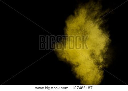 Abstract yellow and gold powder explosion on black background. Paint Holi.
