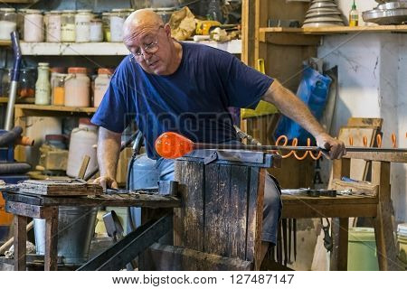 MURANO ITALY - AUGUST 5 2015: Glass worker in action in the Murano glass factory.