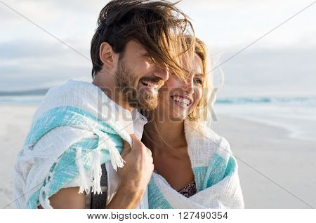 Happy couple wrapped up in blanket at beach. Young couple wrapped in towel on beach. Smiling couple at beach enjoying view of the sea during sunset.