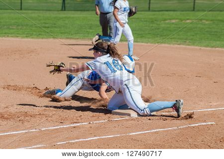Softball runner and defense player collide at first base.