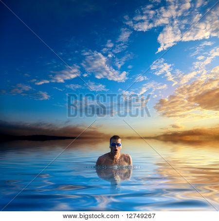 Sonnenuntergang und Schwimmen junger Mann