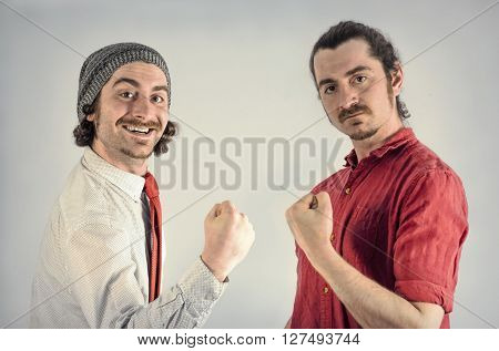 Twin adult men with beards fist pump after victory