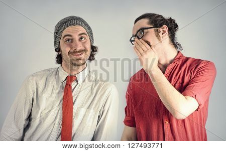 Twin adult men with beards tell secrets to eachother