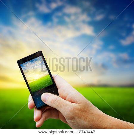 Handy in der Hand und Land-Sonnenuntergang