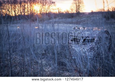 Hunting season in frosty morning in rural field with hunting tent and  hunters  waiting for prey next to the river while beautiful sunrise
