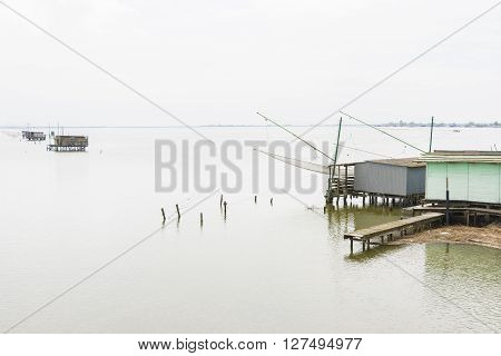 fishing huts on the sea near the city of Comacchio in Italy during a cloudy day