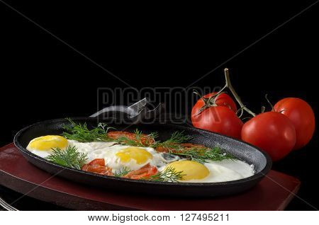 Scrambled eggs with tomatoes in a frying pan on the stand, and the whole tomatoes on black background