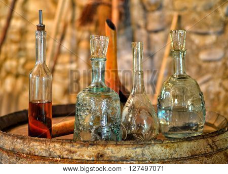 Still life with antique utensils for wine and brandy in the ancient wine cellar on the old oak barrel