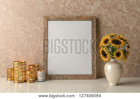 Blank Picture frame on the wall a vase of sunflowers and a candles