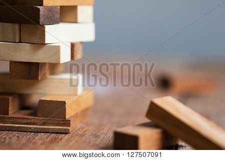 Blank wooden block leaning on a structure made of many other blocks with several of them still lying scattered on a textured rustic wooden desk. Conceptual of leisure game or start up business