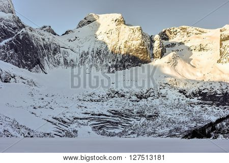 Mountain peaks around Storvatnet in the Lofoten Islands Norway in the winter. poster