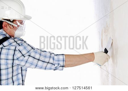 Man in hardhat aligns the walls with stucco