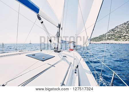 Young blonde woman wearing red shorts, sitting on deck under sails on yacht bow and enjoying wonderful view to cliffs in peaceful sea during summer sailing holidays - yacht charter concept