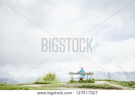 Woman wearing outdoor clothing, sitting on bench on top of mountain in Bavarian Alps with her trekking poles, resting after hiking trail and enjoying view to valley - healthy lifestyle concept