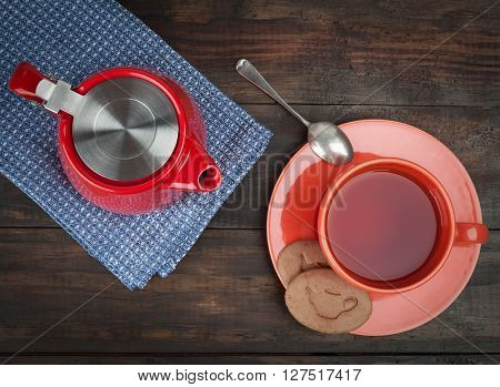Red Teapot With Orange Teacup And Saucer And Cookies