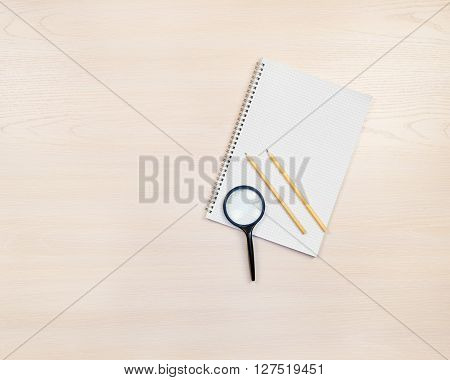 Magnifying glass pencils and notepad on light ?oloured wooden background. poster