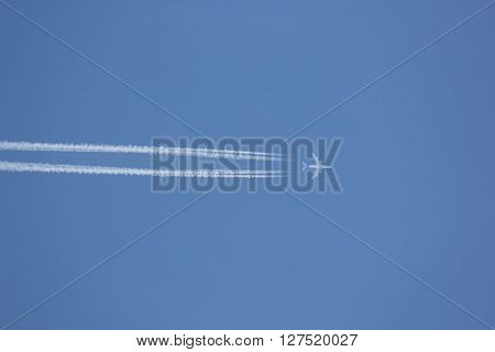 Airplane with contrail against clear blue sky