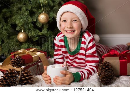 joyful smiling child in santa's hat holding cup of hot chocolate with marshmallows and candy canes being cozy at home and enjoying christmas time by the tree and decorations