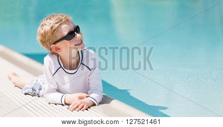 panorama of cheerful little boy enjoying summer vacation by the pool looking at copy space on his side