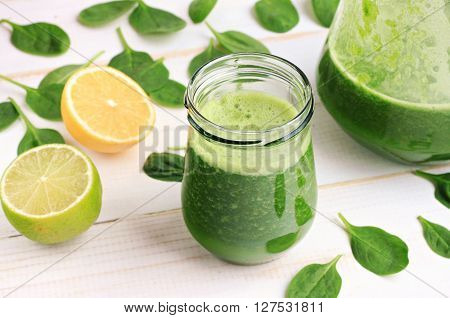 Green fresh leafy greens smoothie in glass jar, spinach leaves, lime, lemon. Refreshing healthy drink.