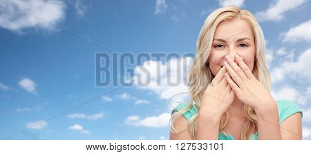 emotions, expressions, embarrassment and people concept - confused young woman or teenage girl wrinkling and closing her nose over blue sky and clouds background