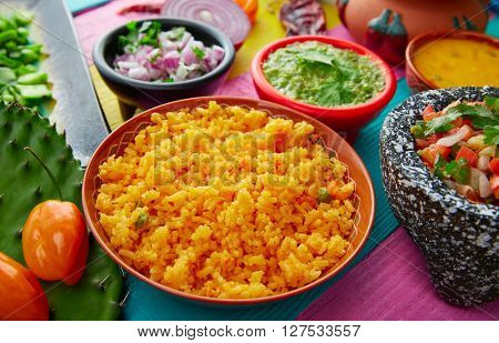 Mexican yellow rice with chili and sauces in colorful background