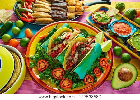 Mexican chicken and beef fajitas tacos in colorful table with sauce