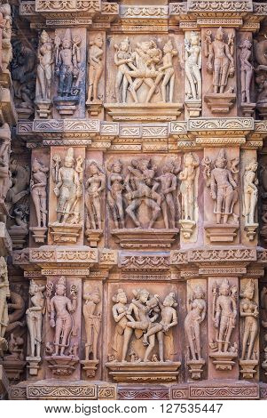 Cultural heritage of India - the sculptures made of sandstone couple in one of Kamasutra's poses deities and people on a wall of the temple of Kandariya-Mahadeva Khajuraho the Province of Madhya Pradesh.