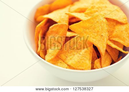 food, junk-food, cuisine and eating concept - close up of corn crisps or nachos in bowl