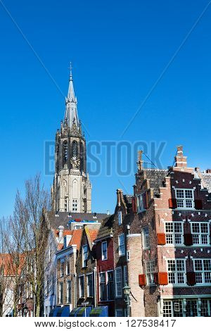 Delft, Netherlands - April 8, 2016: Colorful view with traditional dutch houses, Nieuwe Kerk or New Church in downtown of popular Holland destination