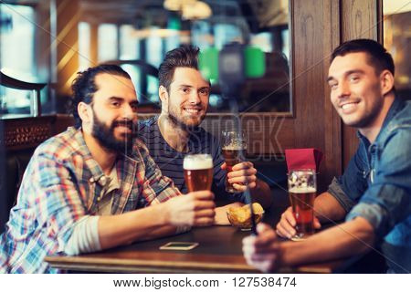 people, men, leisure, friendship and technology concept - happy male friends drinking beer and taking picture with smartphone selfie stick at bar or pub