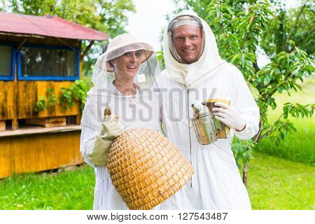 Beekeeper team working outdoor with smoker and beehive
