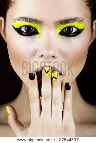 Close-up portrait of girl with yellow and black make-up creative nail art disign. Beauty face. Photo shot in studio