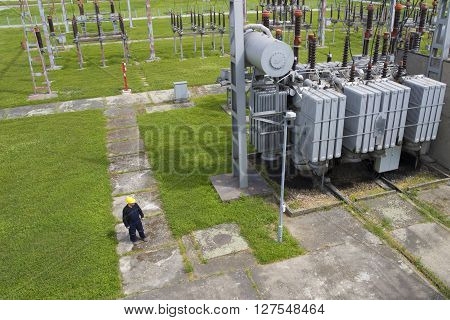 Worker in high voltage switchyard in electrical substation
