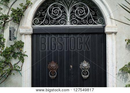Varenna, Italy - September 4th 2015: closeup photo of a black door with elaborate handles at Villa Monastero in Varenna Italy.